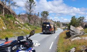 Auf einer Kurvenstrecke in Norwegen fahren Motorräder und das Begleitfahrzeug von ALMOTO Motorrad Reisen.