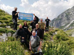 Eine Gruppe Motorradfahrer steht auf einem Berg und freut sich über die Aussicht.